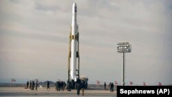 An Iranian rocket carrying a satellite is prepared for launch from an undisclosed site believed to be in the Semnan province, April 22, 2020