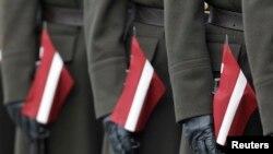 Латвійскія салдаты трымаюць вінтоўкі, упрыгожаныя нацыянальнымі сьцягамі Латвіі падчас ваеннага парада ў Рызе. Ілюстрацыйнае фота