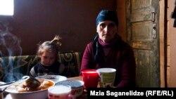 პატარა გოგო და მოხუცი ქალი ეკომიგრანტებისა და სოციალურად დაუცველების დასახლებაში, ხელვაჩაურში. 2014 წელი