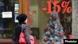 Armenia - A woman walks past a Yerevan shop announcing a Christmas price discount, 20Dec2011.