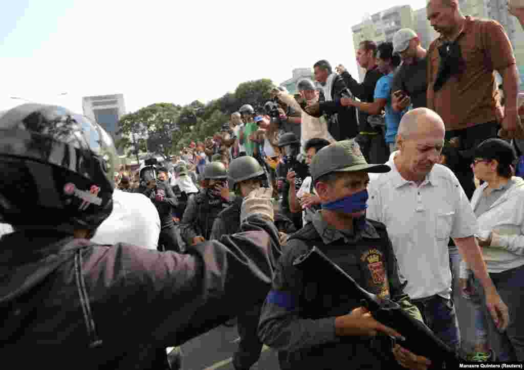Люди плескають військовим, які проходять повз базу Ла Карлота у Каракасі