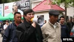 Саясаткер Жасарал Қуанышалин оппозиция шеруіне тосқауыл қойған полициядан жолды ашуды талап етіп тұр. Алматы, 1 мамыр 2010 жыл.