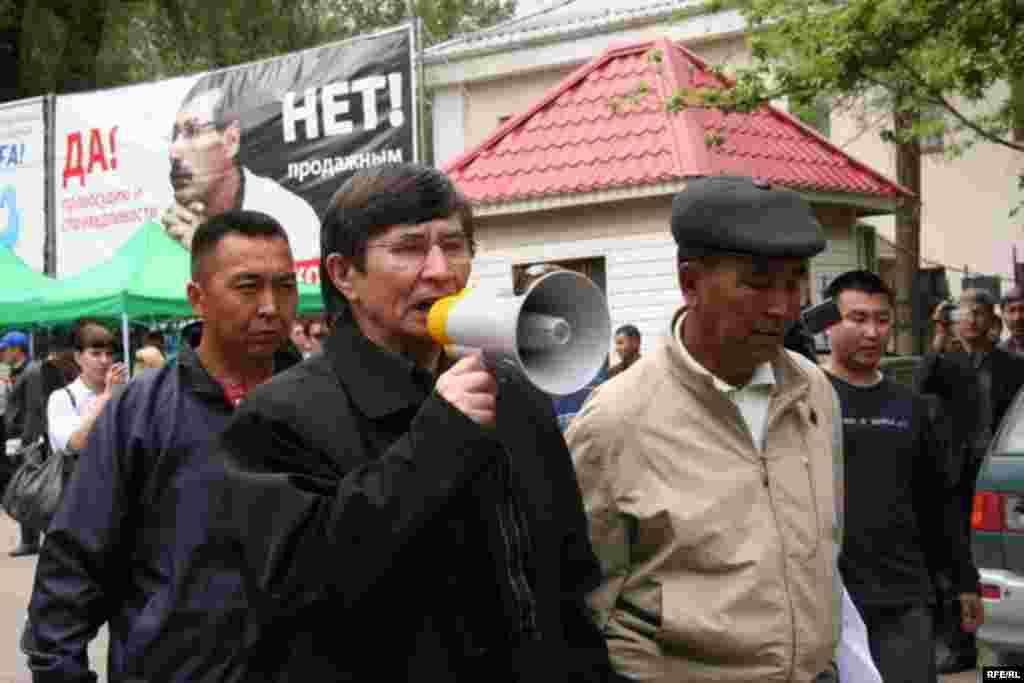 Саясаткер Жасарал Қуанышәлі полицияға қайырылып, оппозиция шеруіне жол беруді талап етіп тұр. Алматы, 1 мамыр 2010 жыл.