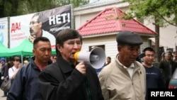 Политик Жасарал Куанышалин требует у полицейских пропустить шествие оппозиции. Алматы, 1 мая 2010 года.