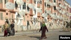 Женщины идут в Туркменабате рядом с жилым домом, на стенах которого установлены спутниковые антенны.
