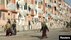 Turkmenistan -- Women walk by a block of flats with satellite TV dishes in the provincial city of Turkmenabat, 07Mar2007