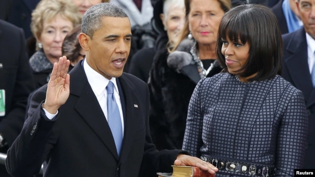 U.S. President Barack Obama (left) recites his oath of office as First Lady Michelle Obama looks on during the swearing-in ceremonies at the U.S Capitol in Washington, D.C., on January 21.