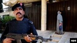 Pakistanda təhlükəsizlik əməkdaşı tibbi bacısını peyvənd işində müşayiət edir