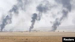 Smoke rises from clashes with Islamic State militants southeast of Mosul in August.