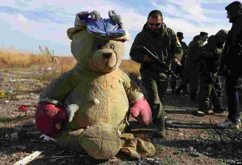 Pro-Russian rebel sappers walk past a giant teddy bear as they search for explosive devices in the destroyed Donetsk International Airport. Ukrainian forces lost control of the airport in January 2015. (AFP/Aleksei Filippov)