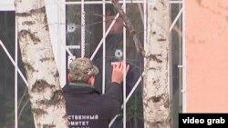 Следователь изучает отверстия от выстрелов на месте происшествия – в школе №263