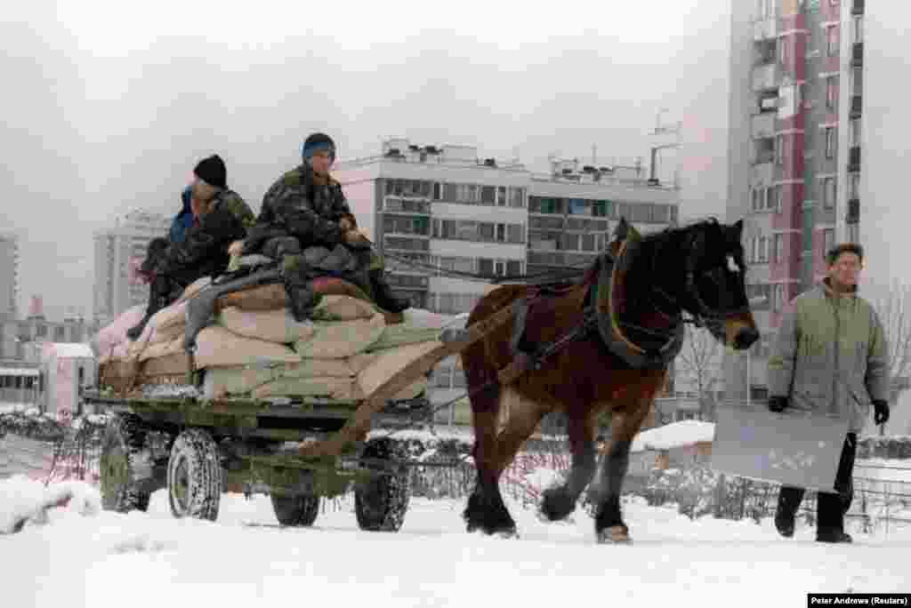 With fuel in short supply, Bosnian army soldiers are forced to use a horse and cart to transport food supplies to the district of New Sarajevo near the airport on January 5, 1995.