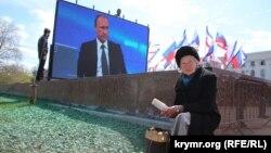 """Женщина на площади в Симферополе, на которой идет трансляция """"прямой линии"""" с президентом России Владимиром Путиным. 16 апреля 2015 года."""