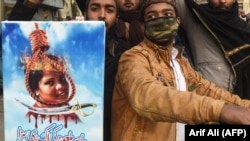 Pakistani Islamists hold a poster displaying the portrait of Asia Bibi, a Christian Pakistani woman accused of blasphemy, during a protest against the Supreme Court decision on Bibi's case in Lahore on February 1.