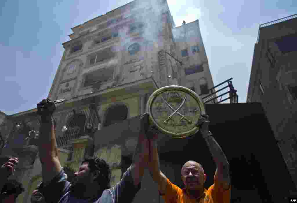 Protesters hold up an emblem of the Muslim Brotherhood removed from the party's headquarters, which was looted and set on fire by angry crowds.