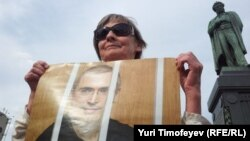 A woman in Moscow holds a portrait of Mikhail Khodorkovsky to mark his continued imprisonment on his birthday in June 2012.