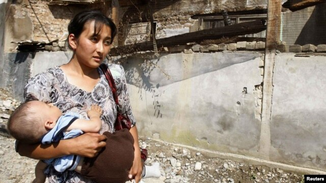 An ethnic Uzbek woman and her child, just returned to Osh from Uzbekistan, walks past a house that was burned down during ethnic clashes.