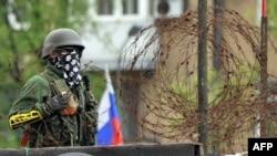 Вооруженный человек стоит рядом с захваченным пророссийскими сепаратистами правительственным зданием. Донецк, 9 мая 2014 года.