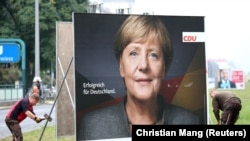 Ангела Меркелдин шайлоо маалындагы Берлиндеги көрнөк-жарнактарынын бири.