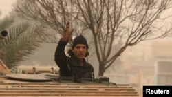 A rebel fighter gestures while riding a military vehicle is western Aleppo. (file photo)