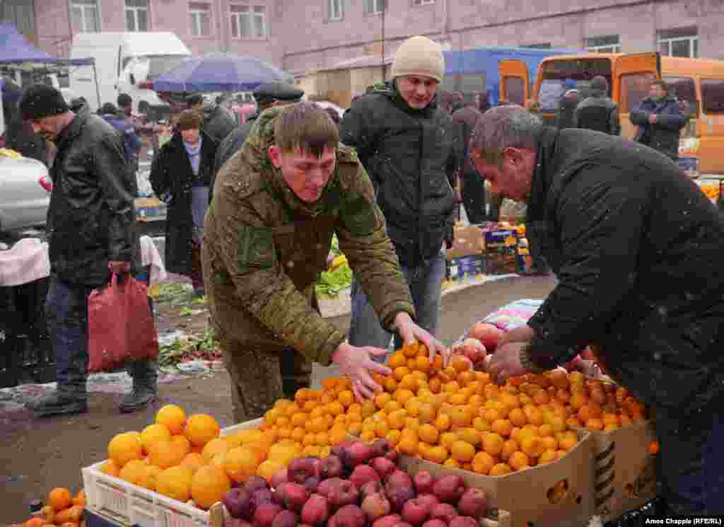 A Russian soldier selecting mandarins in the central market. As part of the investigation into the Avetisian killings, investigators reportedly uncovered a massive fraud operation in which $7.8 million of food intended for Russian soldiers in Armenia was stolen and resold.