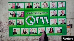 Iraq -- A woman walks past a Patriotic Union of Kurdistan (PUK) campaign poster for Iraq's parliamentary elections in Sulaimaniya, April 28, 2014
