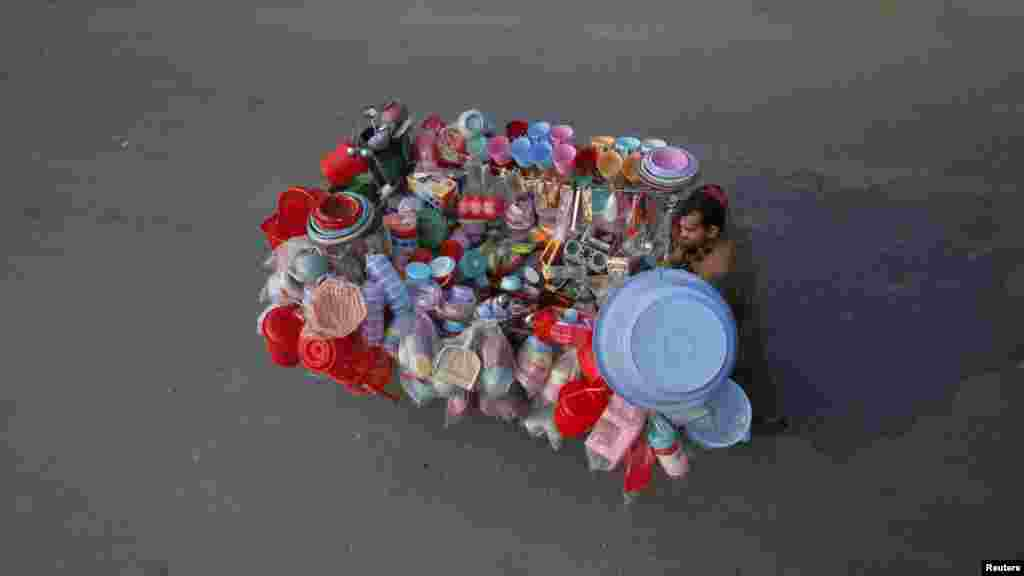 A vendor pushes a cart displaying plastic containers and accessories on a street in Lahore, Pakistan. REUTERS/Mohsin Raza