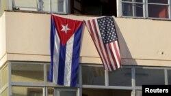 Flamuri kuban (majtas) dhe ai amerikan në një bdlrtesë banimi në Havanë gjatë ditës së sotme