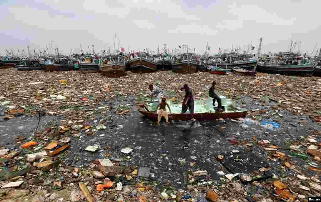 Хлопчыкі на кінутым чоўне перад рыбалоўным портам Карачы (Пакістан) зьбіраюць сьмецьце, якое можна здаць на перапрацоўку.