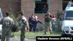 Security forces stand guard outside a school in Beslan while emergency crews work inside in 2004 photo.