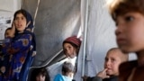 FILE: Internally displaced Afghan children arrive to study inside a tent at a refugee camp in the western province of Herat.