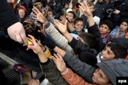 Иракские дети-беженцы получают сладости, прибывшие с гуманитарной помощью. Их родители бежали из районов, занятых боевиками группировки «Исламское государство». Лагерь беженцев Захо, 10 декабря 2014 года.