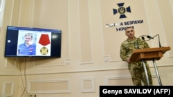 Ukrainian Security Service deputy chief Viktor Kononenko (right) speaks during a press conference as a picture of Kirill Vyshynsky is seen on a screen in Kyiv on May 15.