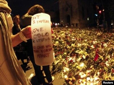 Žena drži sveću u moru cvećepostavljenom u znak sećanja na one koji su ubijeni u bombaškom napadu i pucnjavi u Norveškoj, katredrala u Oslu, 25. jul 2011