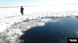 A photo released by Russia's Emergency Situations Ministry on February 15 shows a hole in surface ice on a lake in the Chelyabinsk region thought to have been caused by a meteorite strike earlier the same day.