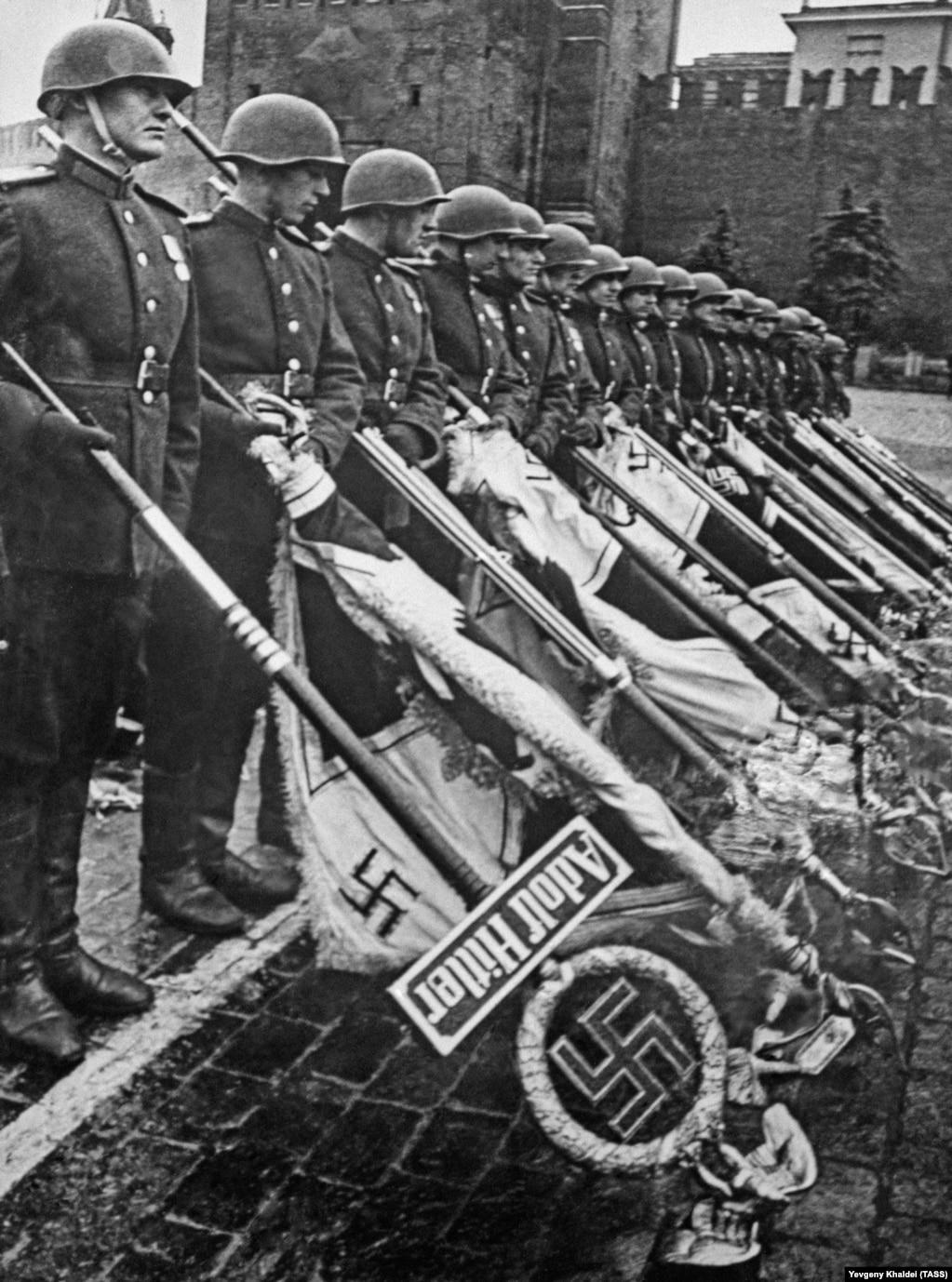 Улуу Ата Мекендик согуштун аяктаганын арналган парадда советтик аскерлер фашисттик армиянын ылдый түшүрүлгөн желектерин кармап турушат. Москва. 24-июнь, 1945-жыл.