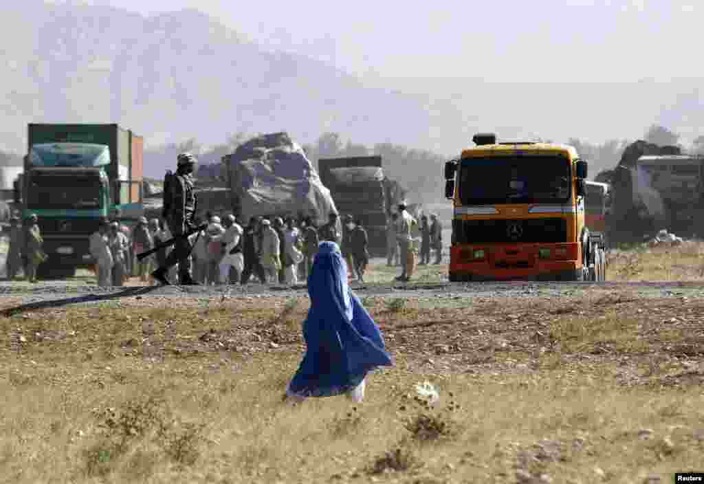 An Afghan woman (center) walks past as Afghan security forces secure the site of burning NATO supply trucks after a Taliban attack in the Behsud district of Nangarhar Province on June 9. (Reuters/Parwiz)