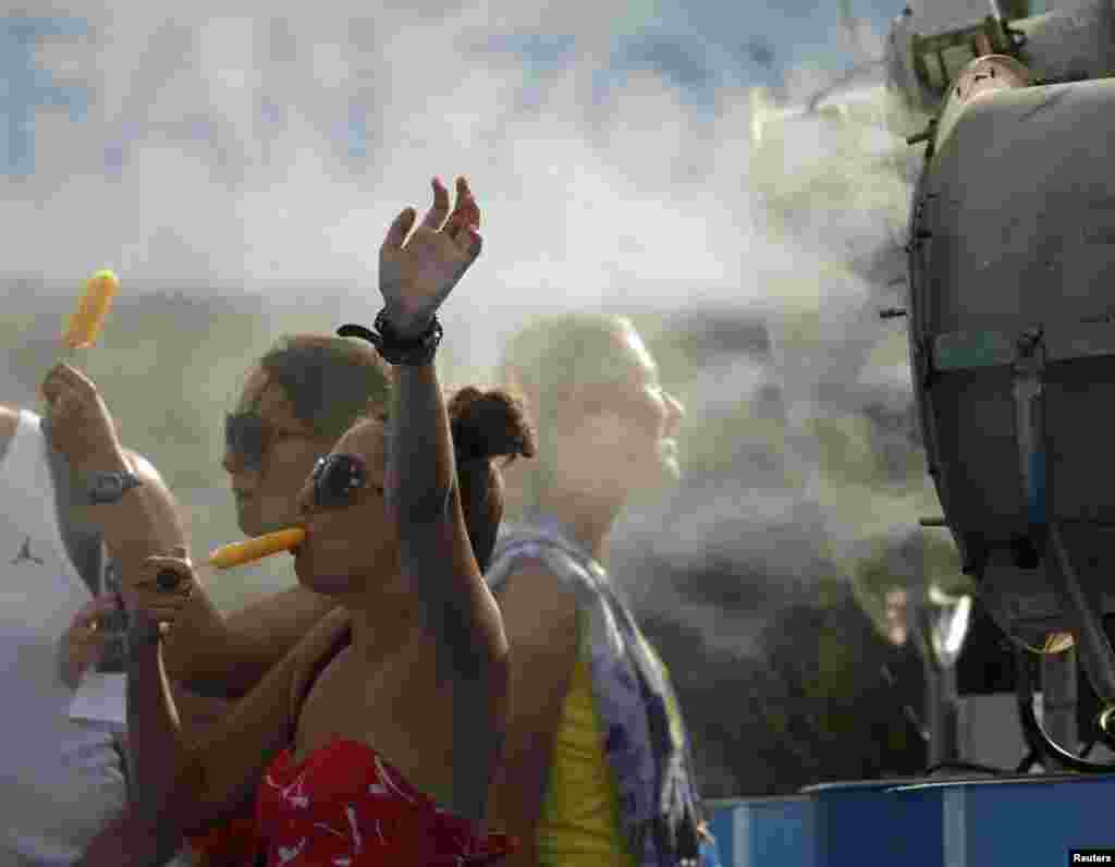 Spectators cool off with popsicles in front of a misting fan on January 15.