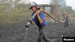 Firefighters work to extinguish fire at a house in Berestyanki in the Ryazan region