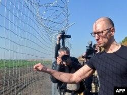Арсений Яценюк осматривает участок стены, возводимой между Украиной и Россией