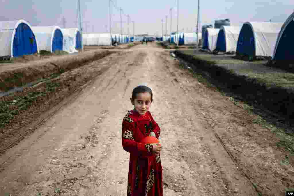 A displaced Iraqi girl who fled violence in the Islamic State (IS) stronghold of Mosul holds a balloon at the Khazer refugee camp near Irbil. (AFP/Dimitar Dilkoff)