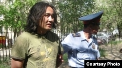 Police arrest activist Aidos Sadyqov in July.