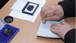 Armenia - An official at a polling station in Yerevan puts a special stamp on a voter's passport which is supposed to prevent multiple voting, 18Feb2013.