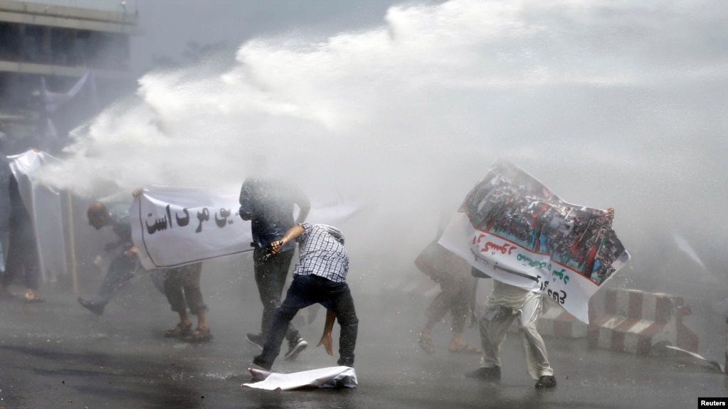 Afghan protesters are hit by a water cannon during a protest in Kabul on June 2.