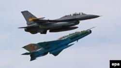 Архівне фото: американський (угорі) і румунський (унизу) винищувачі імітують повітряний бій під час навчань у Румунії