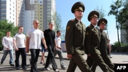 New Belarusian army recruits march behind officers near a recruiting station in Minsk