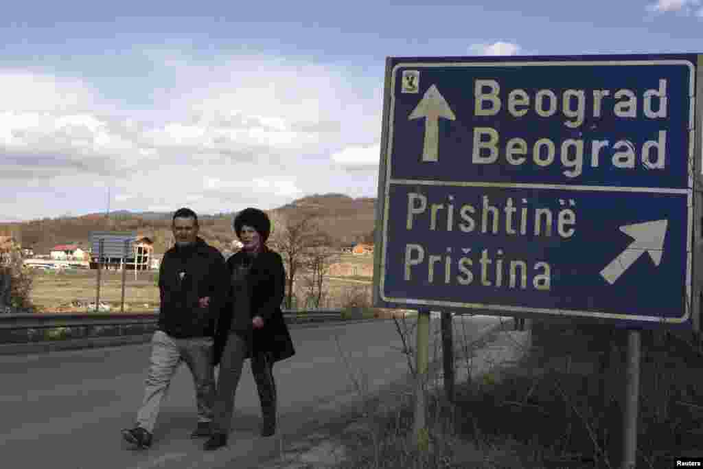 A couple walks past a traffic sign pointing toward the capitals of Serbia and Kosovo.