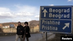 Kosovo -- A couple walks past a traffic sign in the ethnically divided town of Mitrovica, 20Mar2013