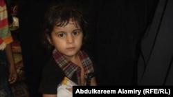 طفل عراقي يتسلّم هدية بيوم اليتيم