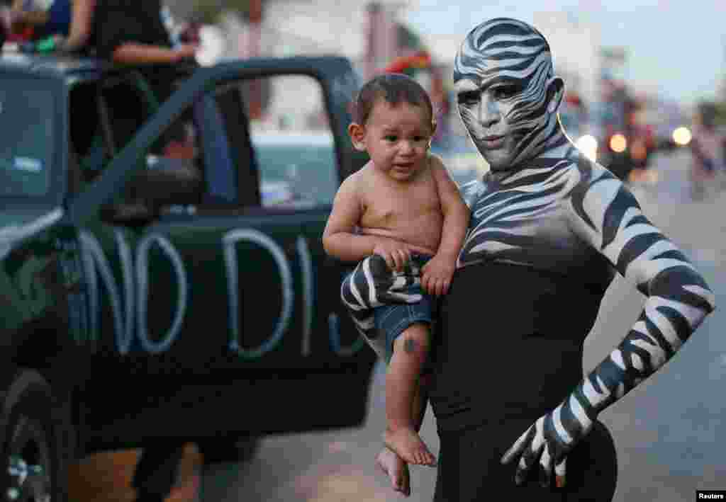 A reveller holds a child while posing for a picture during a gay-pride parade in Ciudad Juarez, Mexico. (Reuters/​Jose Luis Gonzalez)